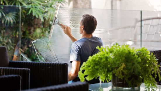 man-in-gray-shirt-cleaning-clear-glass-wall-near-sofa-713297